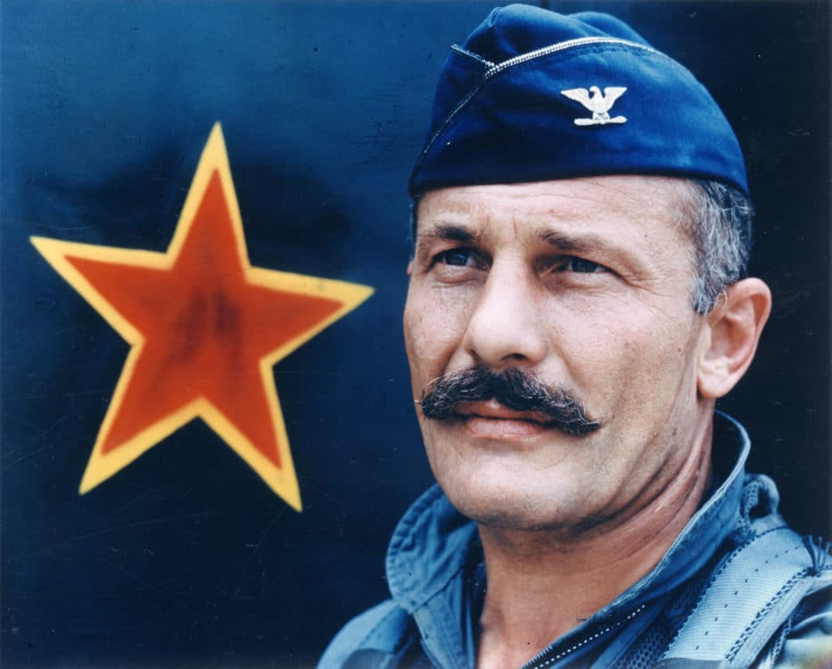 triple ace robin olds in front of an aircraft