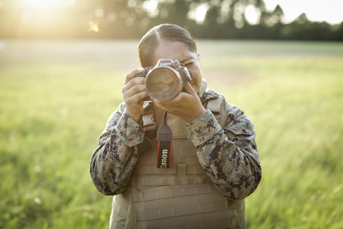 U.S. Marine Corps Lance Cpl. Stephanie E. Soto, a combat photographer assigned to Headquarters and Service Company, Marine Corps Combat Service Support Schools, poses for a photograph after conducting helicopter support teams (HST) exercise at Landing Zone Kite, on Marine Corps Base Camp Lejeune, N.C., July 1, 2019. Lance Cpl. Soto documented entry-level Marines conducting HST exercises. (U.S. Marine Corps Photo by Sgt. Manuel A. Serrano)