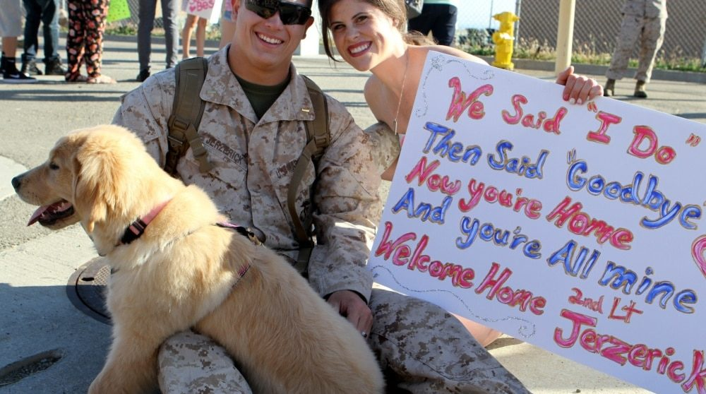 military couple with welcome home sign