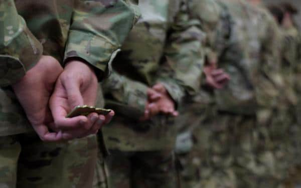 Army coin in soldiers' hands