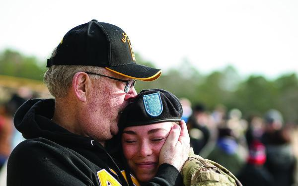 father hugs army daughter  at fort jackson