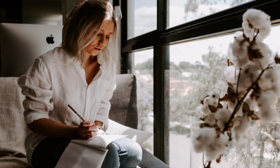 woman writing letter by a window