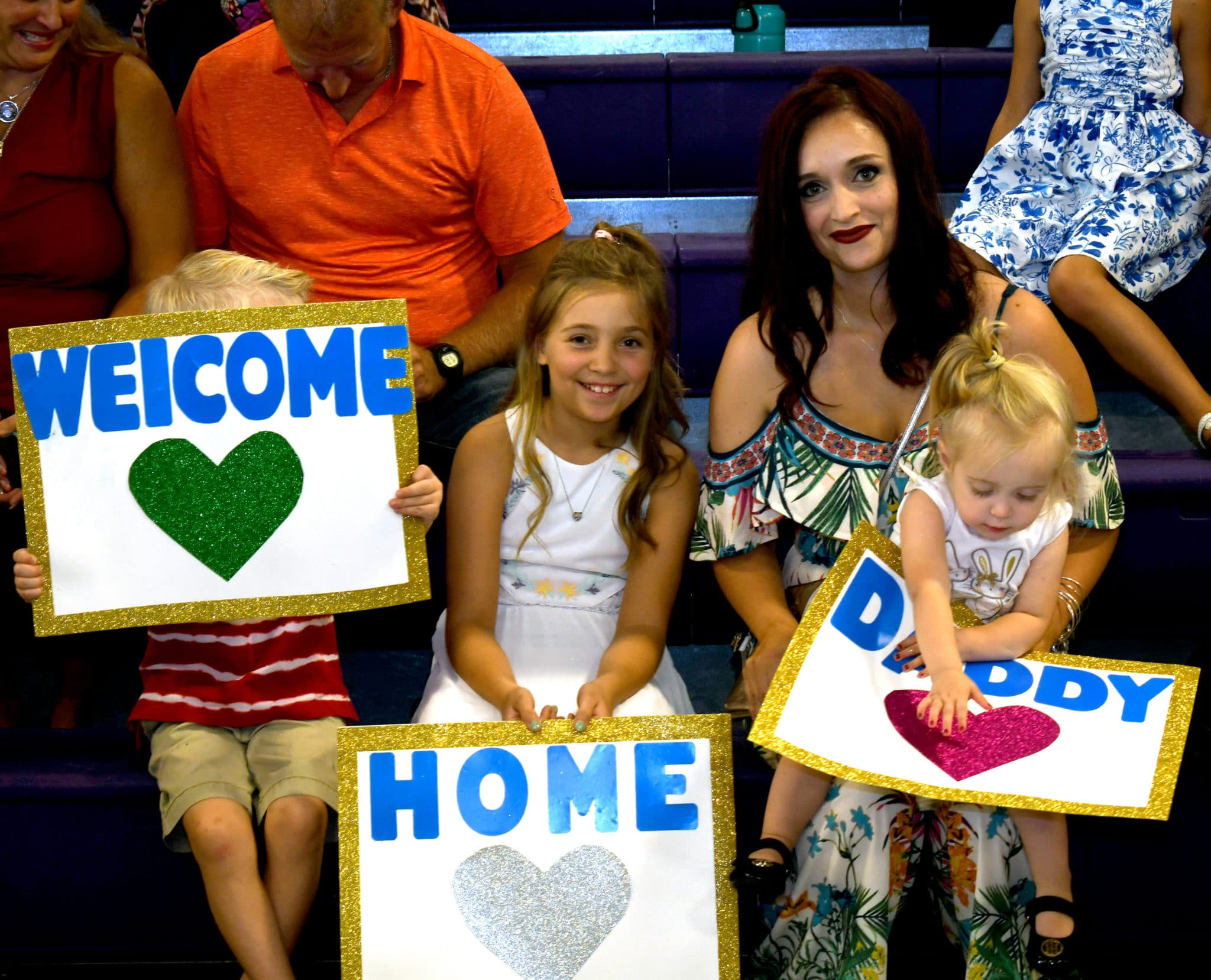 Family members hold up signs to welcome home soldiers with the 1st Armored Brigade Combat Team, 1st Infantry Division (US Army photo by Sgt. Timothy Brokhoff).