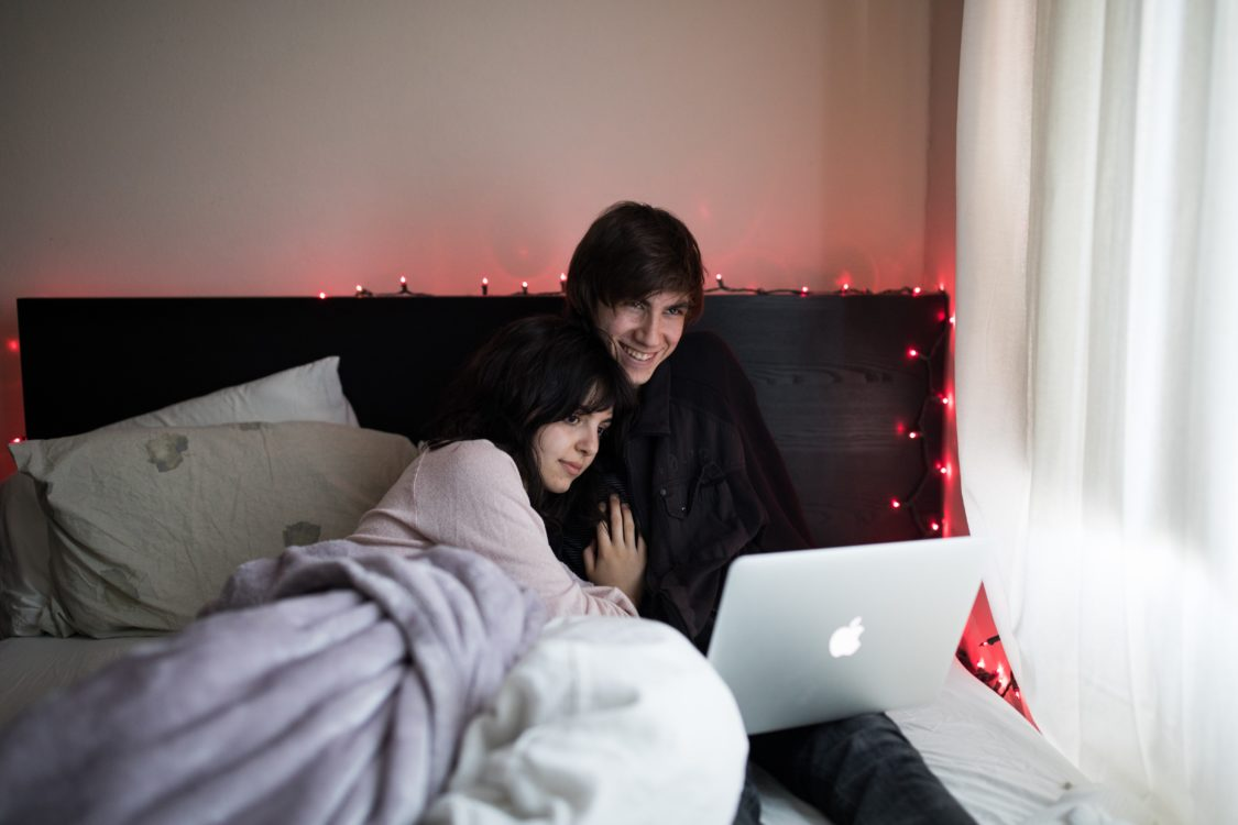 stay at home date night ideas: couple cuddling in bed